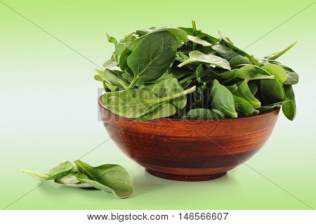Bowl overfilled with spinach on white background