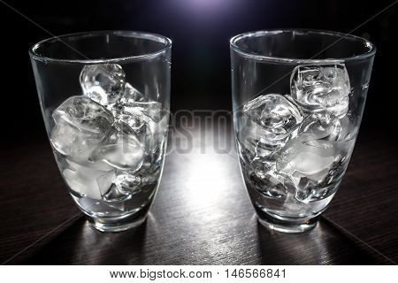 two glasses with ice; few transparent cups with cold icecubes;