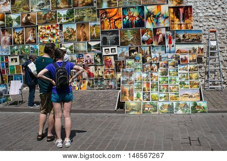 POLAND, KRAKOW - MAY 27, 2016: Tourists admires the outdoor gallery paintings for sale in the historical center of Krakow near the city walls at St. Florian Gate.