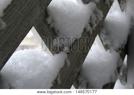 snow clinging to the weathered lattice on my porch