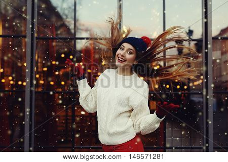 Street fashion portrait of smiling beautiful young woman playing with her long hair. Lady wearing classic winter knitted clothes. Festive garland lights. Magic snowfall effect. Toned.