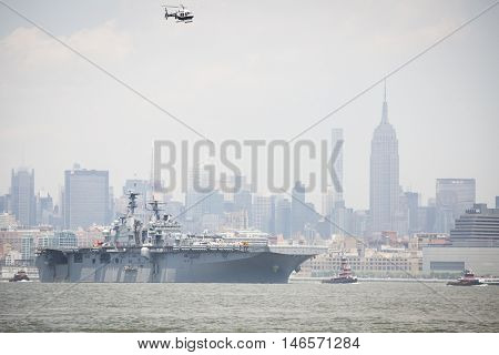 JERSEY CITY NJ - MAY 31 2016: USS Bataan (LHD 5) on the Hudson River passes the Empire State Building upon departing Manhattan marking the end of Fleet Week 2016 as seen from Liberty State Park.