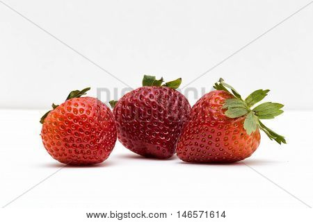 Three delicious strawberries in a white background