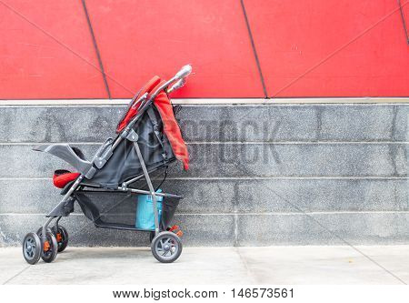 empty red baby Stroller on red background