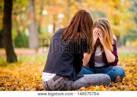 Friends talk outside in autumn nature - one girl is caressing and listening to another teenage girl with problems