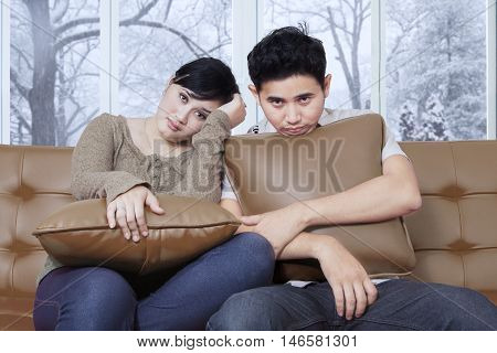 Portrait of two Asian couple sitting on the sofa and looks bored while holding pillow