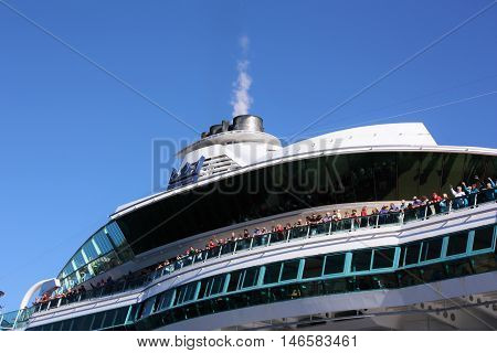 VANCOUVER, BC. AUGUST 21, 2015. Passengers waving goodbye as Royal Caribbean Cruise Lines ship Radiance of the Seas sails on a Alaska cruise.