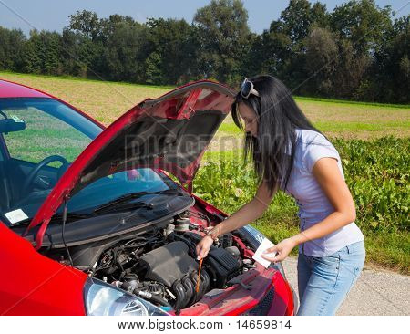 Woman measures the oil pressure in her car