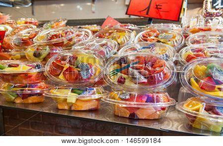 Fruit salad in plasic boxex at La Boqueria market in Barcelona