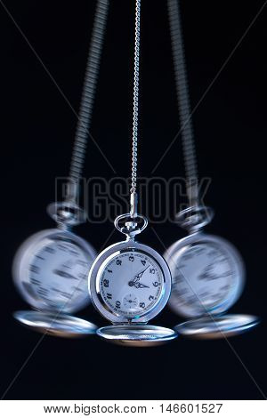 Pocket watch swinging on a chain to hypnotise black background