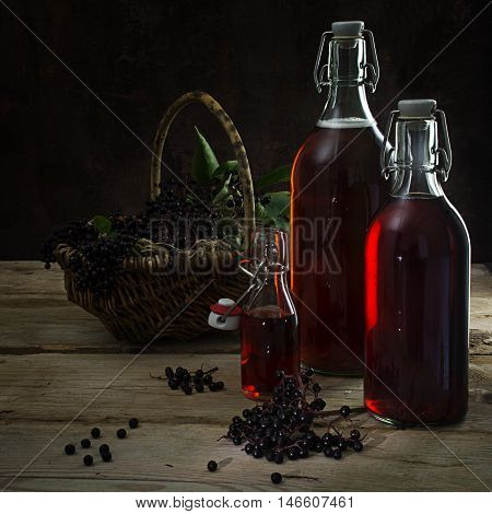 bottles with the red juice from black elderberries (Sambucus nigra) and a basket with berries on rustic wood dark background copy space selected focus