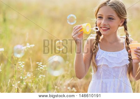 Joyful girl is blowing soap bubbles in meadow. She is standing and laughing