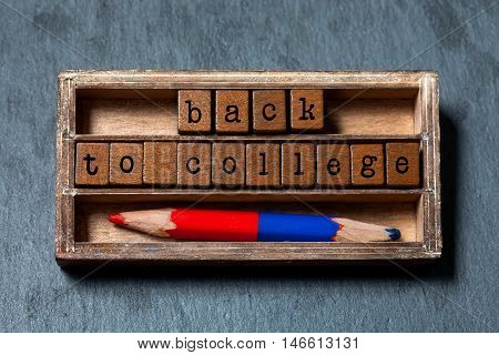 Back to college conceptual image. Vintage blocks with retro style letters, colored pencil, aged wooden box. Gray stone background, macro