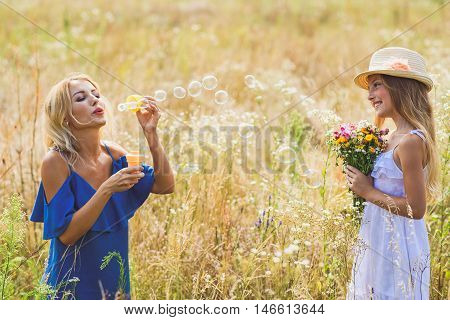 Happy woman is blowing soap bubbles on field with enjoyment. Her daughter is standing and looking at her with interest. She is holding flowers and smiling