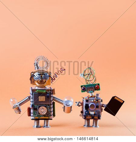 Robot friends concept. Pair robotic circuit socket toy mechanism characters with black microchip lamp bulbs. Funny faces, blue red eyes and glasses. Copy text, light gradient peach color
