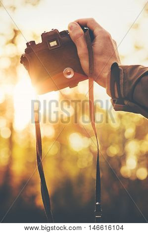 Hand holding retro photo camera shooting sunset outdoor Travel Lifestyle with autumn nature on background