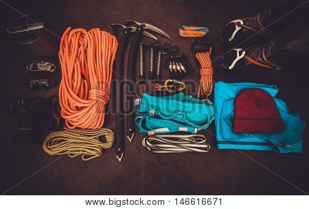Climbing equipment set: orange rope crampons ice axe shoes harness and other set on dark background Travel lifestyle trendy concept top view