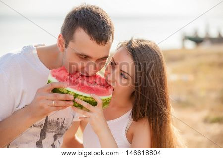 smiling young couple eating fresh melon together