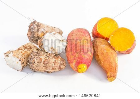 Pile of raw potatoes and taroes on the white background