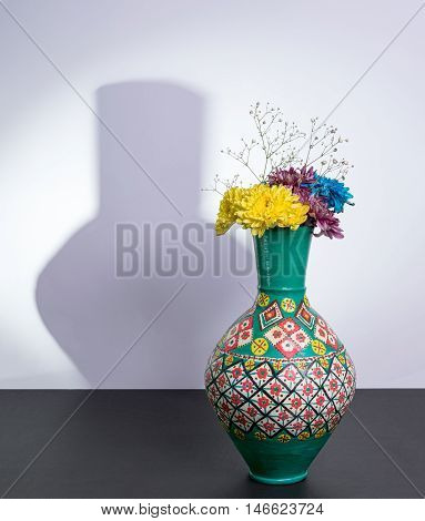 Colorful Egyptian traditional pottery vase three yellow blue and violet flowers with harsh shadow excluding flowers over black table and white wall