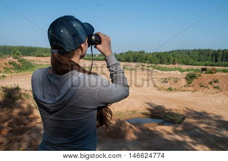 ornithologist girl standing on a cliff with binoculars and bird studies