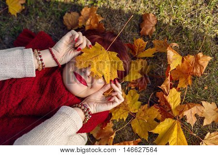 Beautiful young woman with red hair covering face with yellow maple leaf lying on the ground. Outdoor shot. Fall. Copy space.