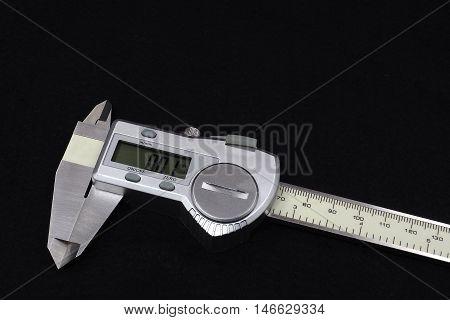 digital vernier caliper (measurement tool) on dark background.