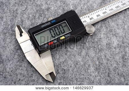 digital vernier caliper (measurement tool) on grey background.