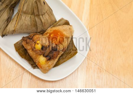 Zongzi is a traditional Chinese food made of glutinous rice stuffed with different fillings and wrapped in bamboo reed or other large flat leaves.