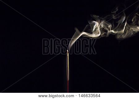 Incense Stick with Smoke on Black in black and white abstract background.