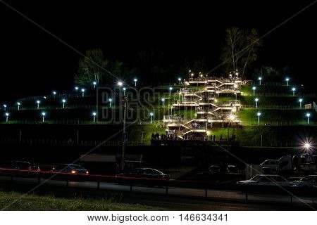 Barnaul Russia. September 11 2016. The warm autumn night people spend their weekends relaxing and walking up the stairs with bright lights leading to the park on the hill