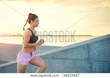 Attractive sporty young woman out jogging running up a steep flight of outdoor steps against an ocean backdrop with the rising sun close up with copy space