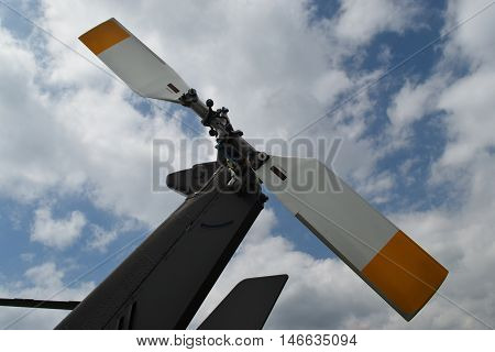 the tail rotor of a helicopter against a cloudy sky