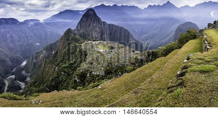 Panoramic shot of the lost Inca city of Machu Picchu with yellow grassland clouds and Huayna Picchu in the background.