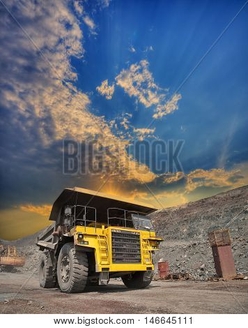 Mining truck loaded withiron ore driving along the opencast on sunset