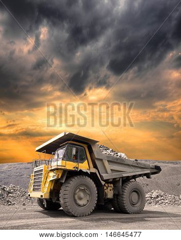 Heavy mining truck driving through the iron ore opencast on stormy sunset