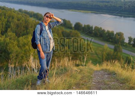Pregnant woman stands on a hill resting after a hard ascent up the mountain. Camping unity with nature.