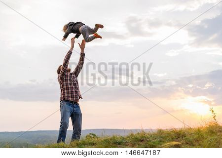 Father tossing up his son. High on a hill in the evening soltse. The concept of oneness with nature family relationships and values. Camping. Playing with your child. Flight and fun. Confidence.