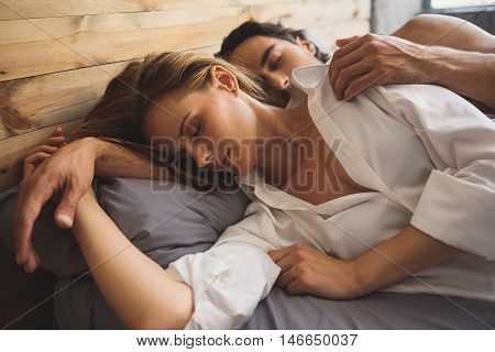 peaceful couple holding their hands while they sleeping