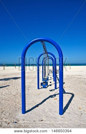 A Large Blue Metal Swing Set on a Sandy Beach