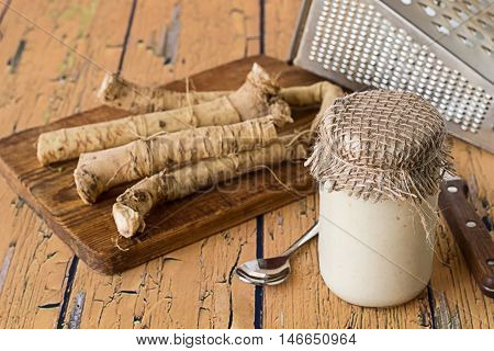 Jar with cooked horseradish, horseradish root on a cutting board, knife and grater on a wooden table.