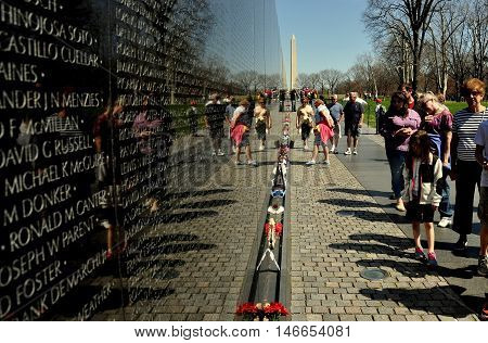 Washington DC - April 10 2014: Visitors viewing the black granite wall inscribed with falen soldier's names at the Vietnam War Memorial on the National Mall