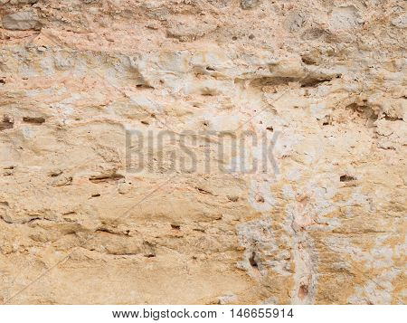 light old rough wall made of natural sandstone with potholes and smudges on the street