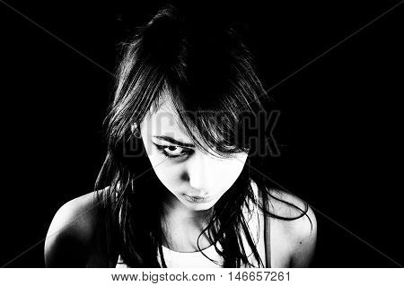 Heavily made-up teen girl looks angry over black background