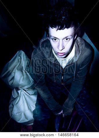 Drunk young man staring forward, flashlight used