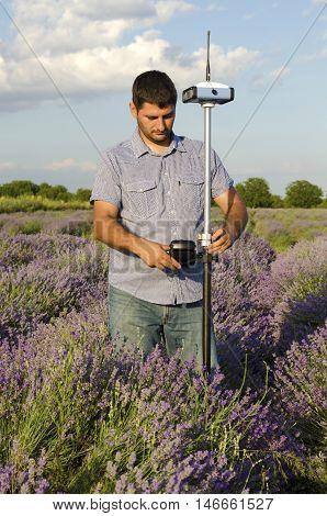 Surveyor adjusting its instrument in a field of lavender