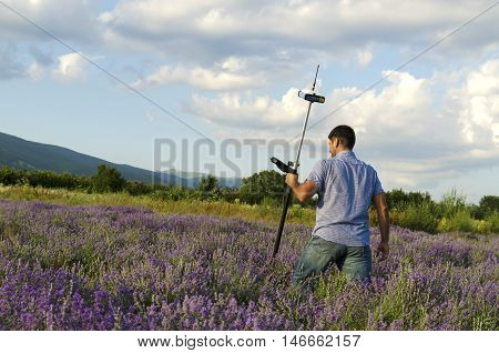 Land surveyor crossing lavender field with controller