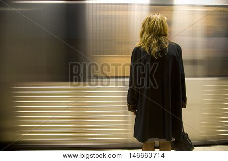 A woman stands alone on a station platform as a train rushes by in a blur.
