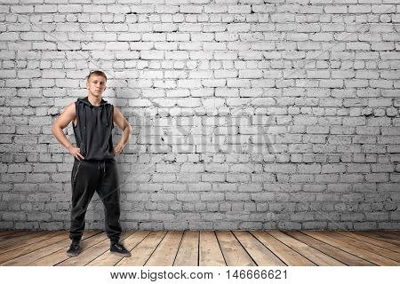 Front view of muscled young man standing with his hands on hips on the background of white brick wall. Wellbeing. Muscleman. Workout and fitness.