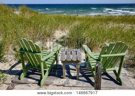 Pair of wooden chairs overlooking seashore and beach